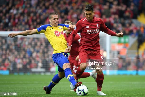 Southampton's Spanish midfielder Oriol Romeu vies with Liverpool's Brazilian midfielder Roberto Firmino during the English Premier League football...