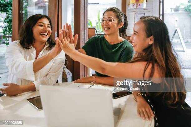 southeast asia female  entrepreneurs high five for success - indonesia stock pictures, royalty-free photos & images