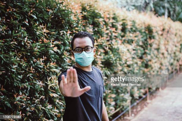 southeast asia man wearing mouth mask and stop hand sign - air respirator mask stock pictures, royalty-free photos & images