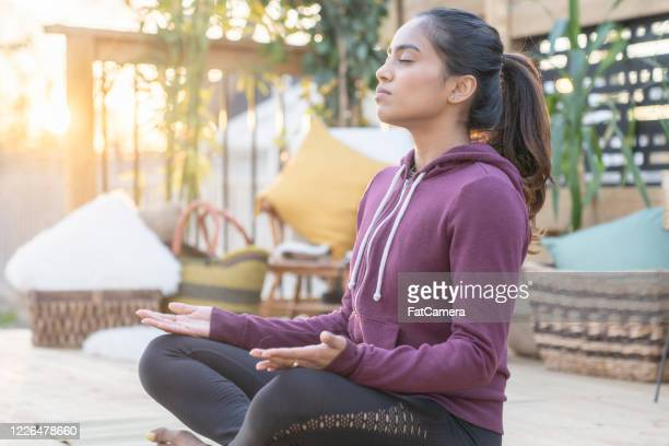 southeast asian female doing yoga on her deck during sunset - fatcamera stock pictures, royalty-free photos & images