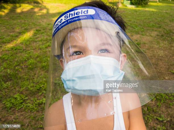 a southeast asian male toddler is wearing a protective face mask and face shield in the park - daily life in philippines stock pictures, royalty-free photos & images