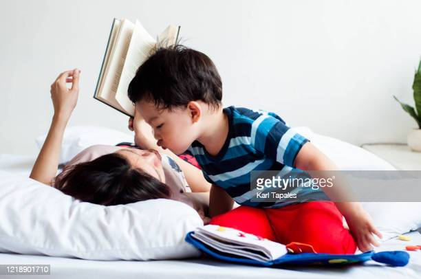 southeast asian mother and son are reading book on the bed - daily life in philippines stock pictures, royalty-free photos & images
