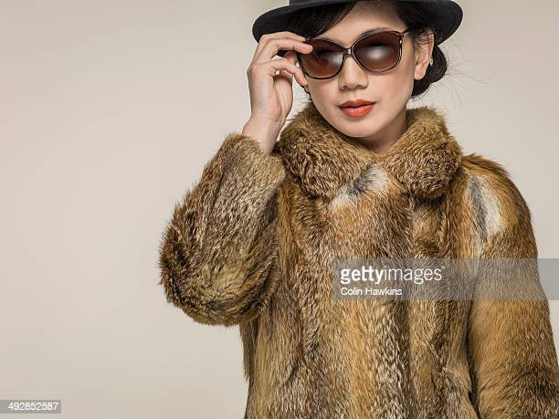 Southeast Asian woman in fur coat and sunglasses