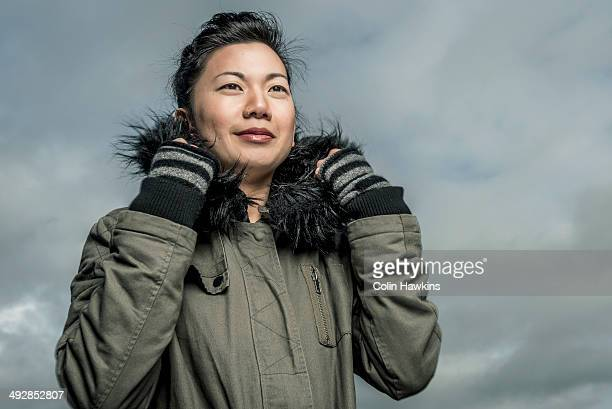 southeast asian woman in winter jacket - colin hawkins stock pictures, royalty-free photos & images