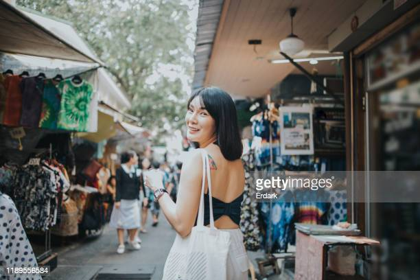 southeast asian women at second hand street market in bangkok - flea market stock pictures, royalty-free photos & images