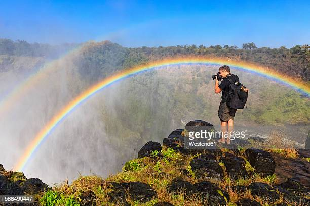 Southern Africa, Zimbabwe, Victoria Falls, photographer with rainbow