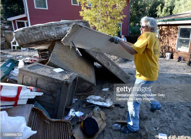 Southern Baptist Disaster Relief volunteer Barb Headrick throws damaged drywall into a pile while cleaning a flood damaged in Jamestown on Saturday...