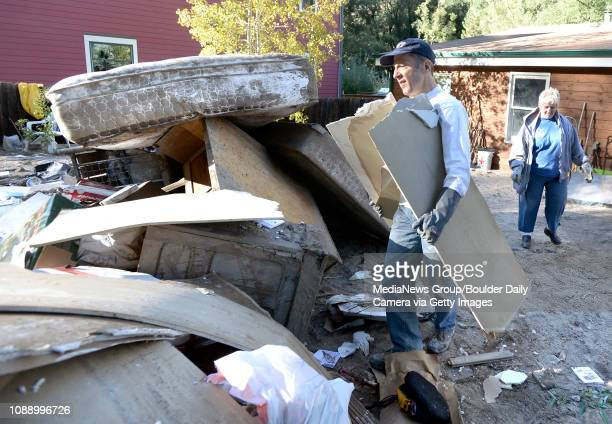 Southern Baptist Disaster Relief volunteer Steve Winkelman of Arvada throws damaged drywall into a pile of flood damaged belongings at a home in...