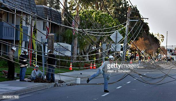 A Southern California Edison worker makes his way through tangled and toppled power lines from ten broken power poles after strong santa ana winds...