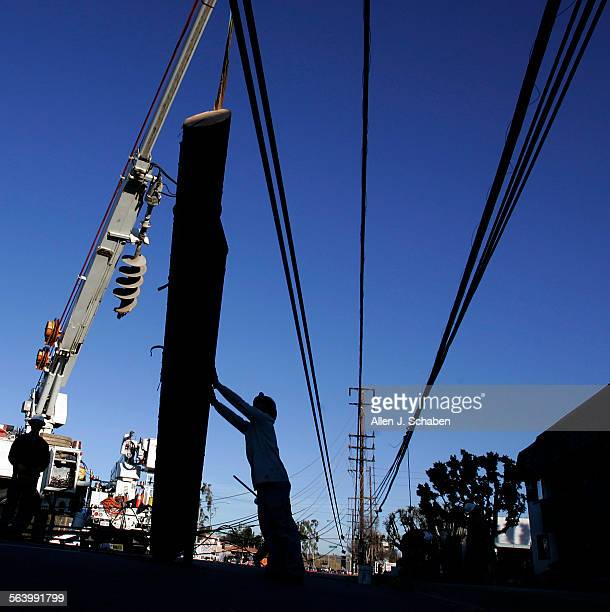 Southern California Edison workers remove a broken power pole amid tangled and toppled power lines from ten broken power poles after strong santa ana...
