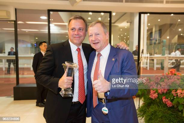 Southern Legend's trainer Caspar Fownes and HKJC's Chief Executive Officer Winfried EngelbrechtBresges celebrate after winning the Kranji Mile at...