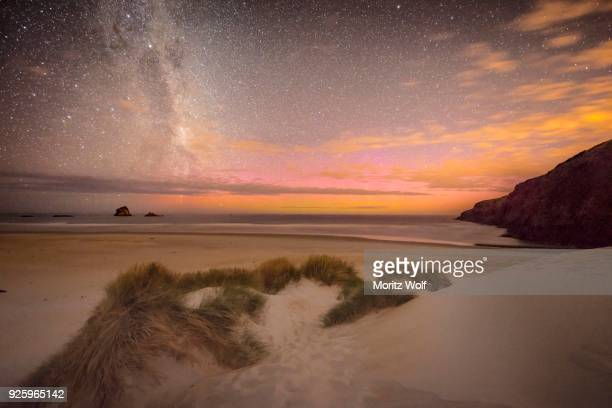 southern lights, aurora australis with milky way above the sea, sand dunes, sandfly bay, dunedin, otago, otago peninsula, southland, new zealand - aurora australis stock pictures, royalty-free photos & images