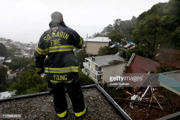 Southern Marin Firefighter Patrick Young looks at a home that was swept down a hill by a mudslide during a rain storm on February 14 2019 in...