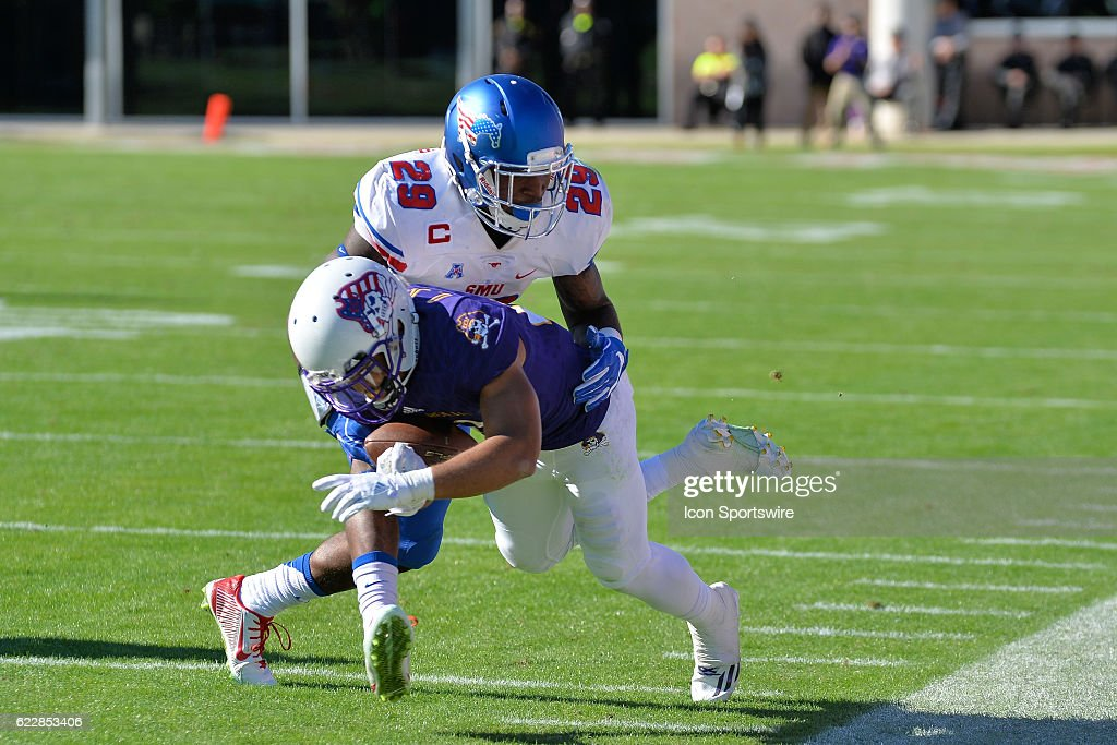 Southern Methodist Mustangs defensive back Darrion Millines (29) tackles East Carolina Pirates wide receiver Quay Johnson (23) along the sidelines during an NCAA football game between the East Carolina Pirates and SMU Mustangs on November 12, 2016 at Dowdy-Ficklen Stadium in Greenville, NC.