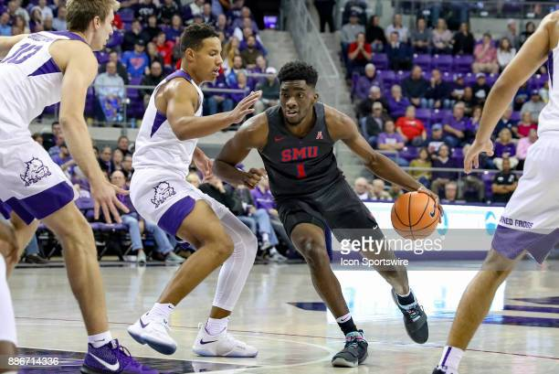 Southern Methodist Mustangs guard Shake Milton drives the lane around TCU Horned Frogs guard Desmond Bane during the game between the SMU Mustangs...