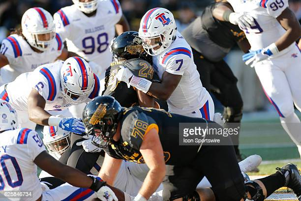 Southern Miss Golden Eagles running back George Payne is tackled by Louisiana Tech Bulldogs safety Xavier Woods during an NCAA football game between...
