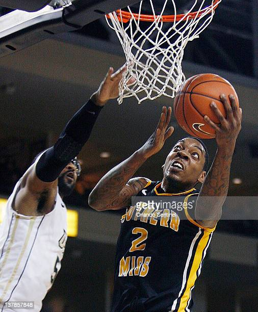 Southern Miss guard Darnell Dodson scores past Central Florida guard Mardus Jordan during game action at UCF Arena in Orlando Florida Saturday...