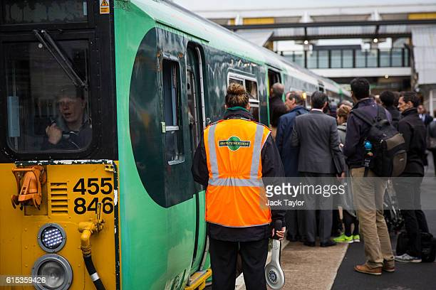 Southern rail conductor waits as commuters board a train at East Croydon station on October 18 2016 in London England Staff at Southern rail have...