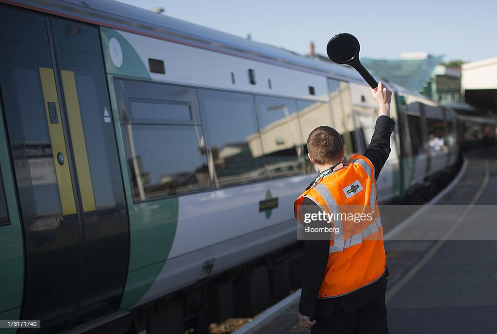 A Southern Railway Ltd. employee signals to the driver of a passenger train from a platform at Clapham Junction rail station in London, U.K., on Tuesday, July 9, 2013. U.K. Prime Minister David Cameron is committed to the building of a high-speed rail line linking London to northern England, his spokesman said as evidence mounts that all-party support for the project is fracturing. Photographer: Simon Dawson/Bloomberg via Getty Images