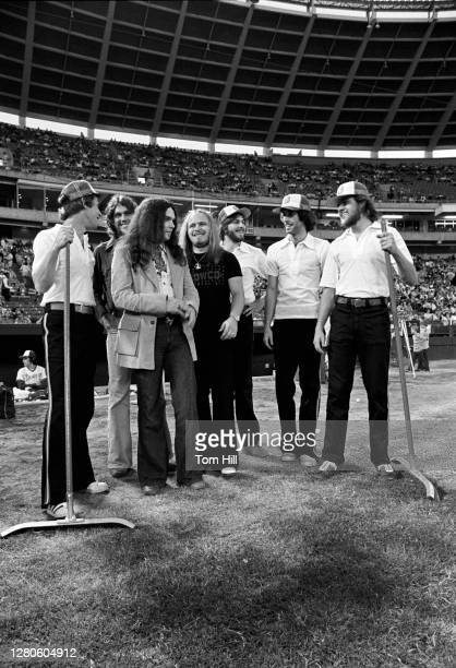 Southern rock band Lynyrd Skynyrd guitarists Steve Gaines and Gary Rossington and singer-frontman Ronnie Van Zant pose with members of the infield...