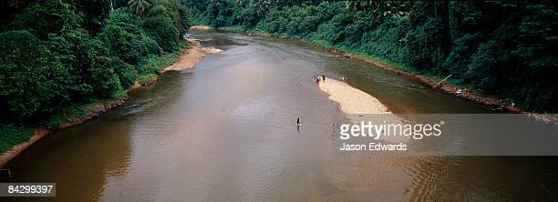 People bathe in a river wending it?s way through tropical rainforest.