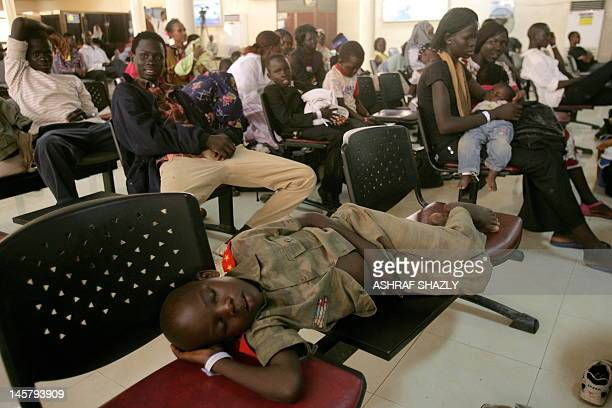 A Southern Sudanese boy sleeps on chairs in the departure lounge of Khartoum's International airport on June 6 part of the last group of 100...