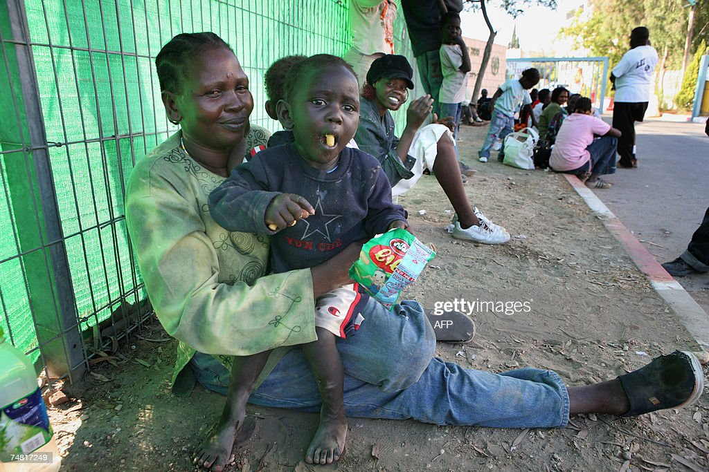Southern Sudanese refugees sit on the pa... : News Photo
