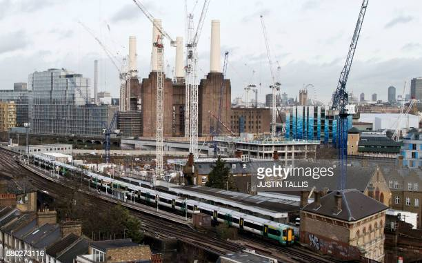 Southern Trains passenger trains pass through Battersea Park rail station as construction work continues on the Battersea Power Station residential...