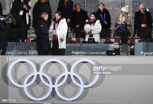 South Korean President Moon Jae and his wife Kim Jung-sook are greeted by German IOC president Thomas Bach at the opening ceremony of the Winter...