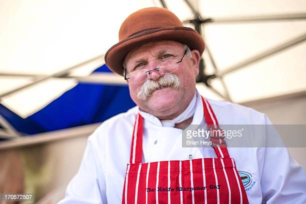 Southport Food Festival, 2013. A stall holder wearing a brown bowler hat and a red and white striped apron.