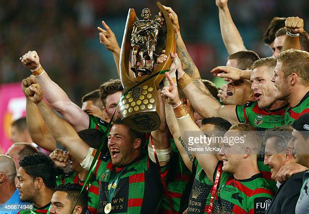 Souths players celebrate with the Provan Summons trophy after their teams win at the 2014 NRL Grand Final match between the South Sydney Rabbitohs...