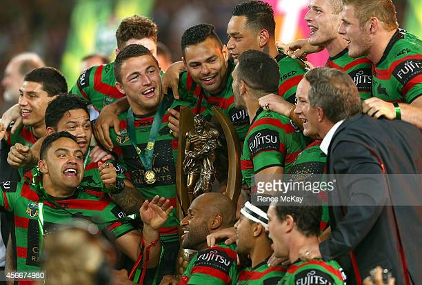 Souths players Sam Burgess and Ben Te'o celebrate with the Provan Summons trophy after their teams win at the 2014 NRL Grand Final match between the...