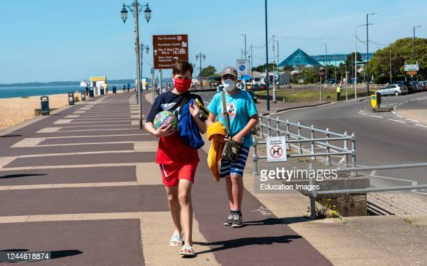 Southsea, Portsmouth, England, Social distancing not being observed. Not 2 metres apart on the seafront in Southsea UK. Covid-19. Two boys wearing...