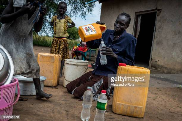 19 OCT 2015 SouthSudan Abuyung village Lake State Adut Lueth unknown age 4 children pregnant of the the 5th prepares an alcholic local brew called...