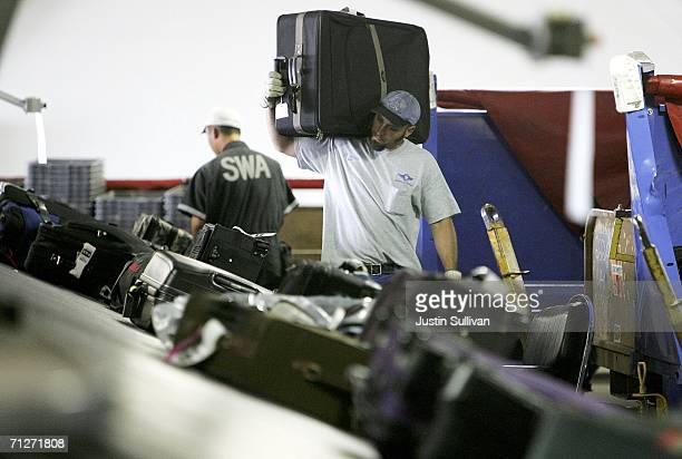 Southwest Airlines baggage handler carries a piece of screend luggage at the Oakland International Airport June 22 2006 in Oakland California The TSA...
