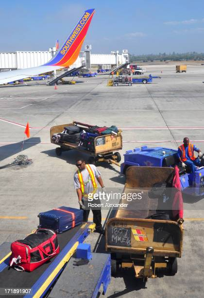 Southwest Airlines baggage handler loads passenger baggage onto an aircraft at Los Angeles International Airport in Los Angeles California