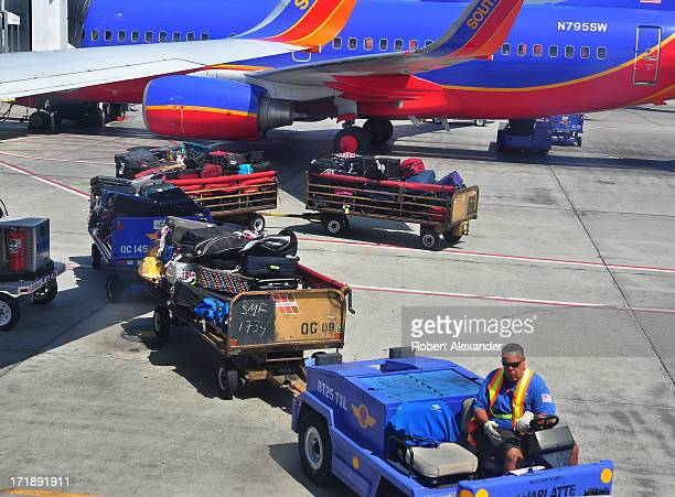 Southwest Airlines baggage handler pulls several carts filled with passenger baggage to be loaded aboard departing aircraft at Los Angeles...