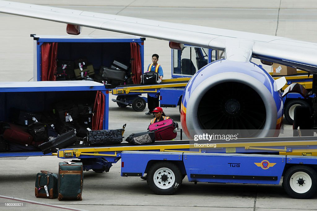A Southwest Airlines Co. employee unloads baggage from a plane sitting on the tarmac at Minneapolis-St. Paul International Airport (MSP) in Minneapolis, Minnesota, U.S., on Sunday, Sept. 8, 2013. Yields on benchmark securities climbed to almost two-year highs as consumers spent more on travel and tourism while manufacturing expanded modestly from early July through late August, according to the Federal Reserves Beige Book. Photographer: Patrick T. Fallon/Bloomberg via Getty Images