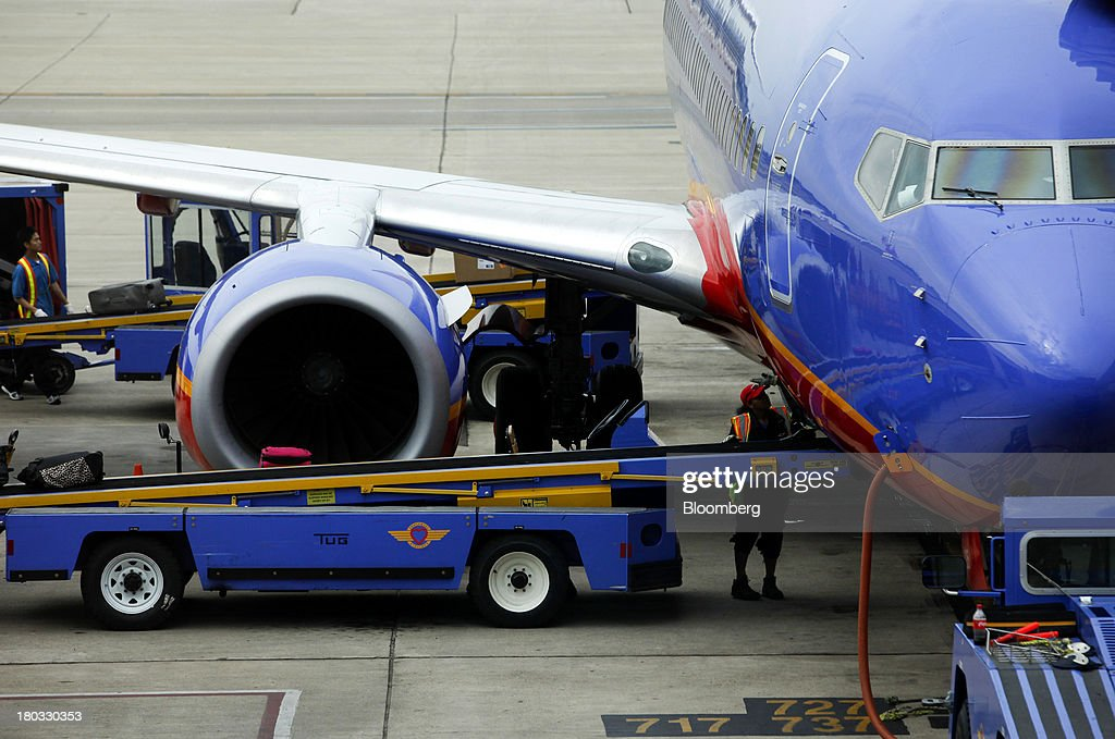 A Southwest Airlines Co. employee waits to unload baggage from a plane sitting on the tarmac at Minneapolis-St. Paul International Airport (MSP) in Minneapolis, Minnesota, U.S., on Sunday, Sept. 8, 2013. Yields on benchmark securities climbed to almost two-year highs as consumers spent more on travel and tourism while manufacturing expanded modestly from early July through late August, according to the Federal Reserves Beige Book. Photographer: Patrick T. Fallon/Bloomberg via Getty Images