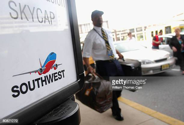 Southwest Airlines employee carries baggage at Philadelphia International Airport May 10 2004 in Philadelphia Pennsylvania Southwest Airlines...