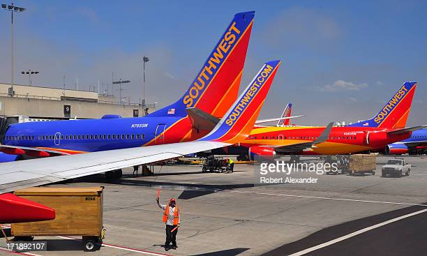 Southwest Airlines ground crew worker with light wands helps guide an aircraft away from the gate at Los Angeles International Airport in Los Angeles...