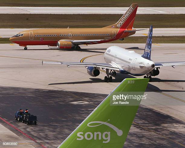 Southwest Jetblue and Song lowcost airline planes sit on the tarmac at the Fort Lauderdale Internatational Airport May 18 2004 in Fort Lauderdale...