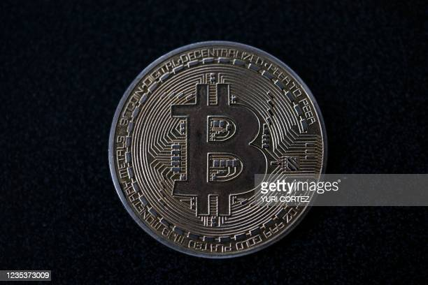 Souvenir coin depicting a bitcoin is pictured in Caracas on September 17, 2021. - According to a study by several universities, 96% of the population...