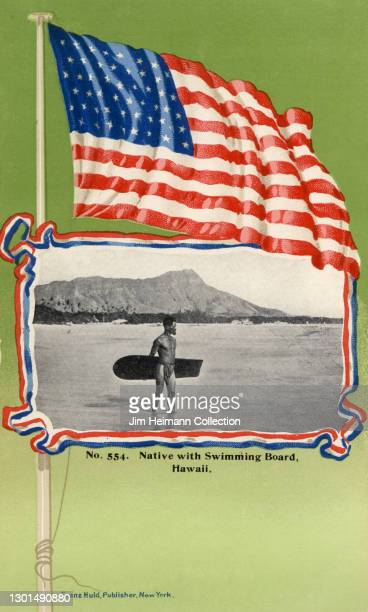Souvenir postcard features a photograph of a native Hawaiian surfer on the beach at Waikiki framed by an illustration of the American flag, circa...