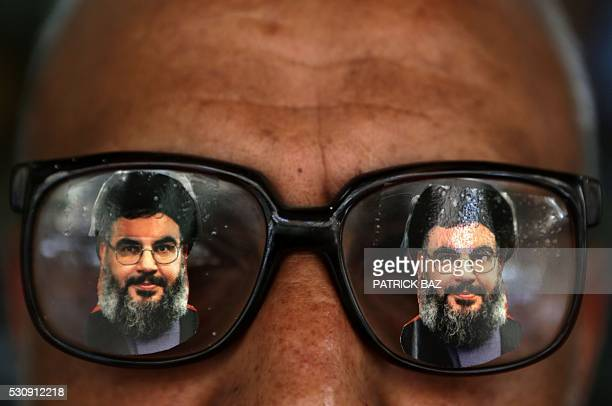 A souvenir shop owner displays glasses decorated with pictures of Hassan Nasrallah the head of Lebanon's powerful Shiite militant group Hezbollah in...