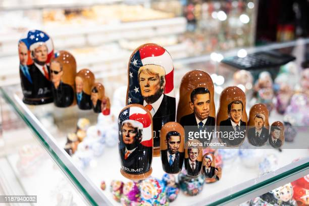 A souvenir shopkeeper displays Matryoshka dolls featuring US presidents including Donald Trump on December 3 2019 in Moscow Russia