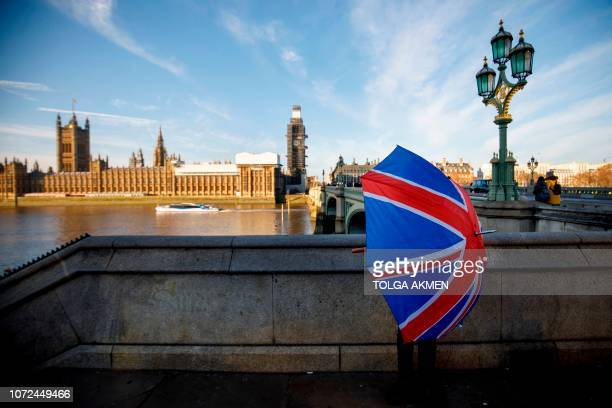 A souvenir stall holder opens a Union Flag umbrella as he arranges his stock opposite the Houses of Parliament on the southern bank of the River...