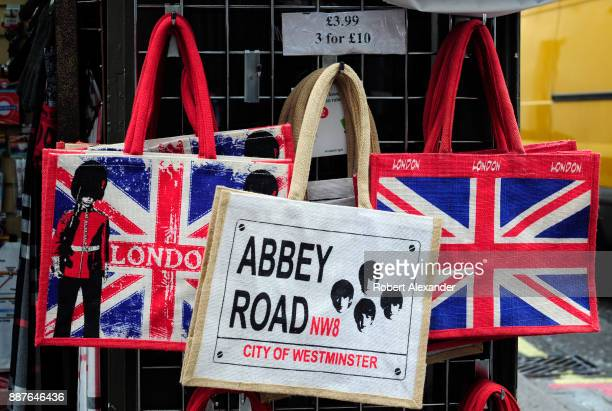 Souvenir tote bags for sale in a London England shop are imprinted with British flags and photographs of The Beatles with the name of the London...