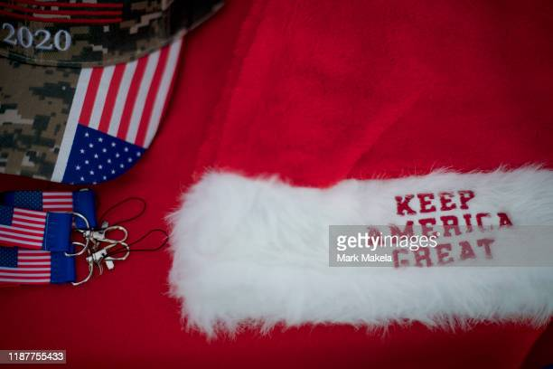 """Souvenir vendors display a Santa Claus hat stating """"KEEP AMERICA GREAT"""" and a """"2020"""" hat before U.S. President Donald J. Trump holds a campaign rally..."""