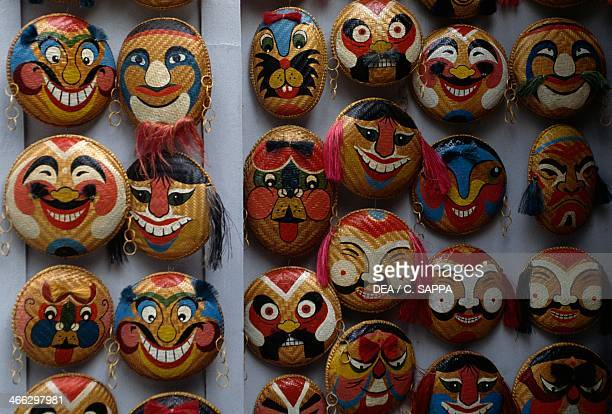 Souvenirs made of straw bowls decorated with colourful faces Hanoi Viet Nam